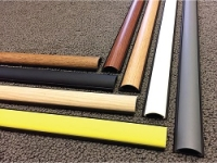 variety of chordsaver cord cover colors laid out on carpet floor.