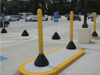 yellow plastic bollard post with black rubber base in use in parking lot