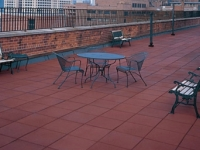 terra cotta rubber rooftop paver in use on rooftop patio.